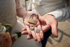 Hochzeitsvorhängeschloß an Hand des Braut- und Bräutigamabschlusses oben stockbilder