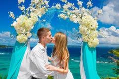 Hochzeitszeremonie auf einem tropischen Strand im Blau Glücklicher Bräutigam und Br Stockfotografie