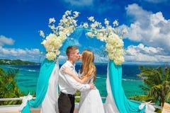Hochzeitszeremonie auf einem tropischen Strand im Blau Glücklicher Bräutigam und Br Lizenzfreies Stockfoto