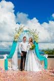Hochzeitszeremonie auf einem tropischen Strand im Blau Glücklicher Bräutigam und Br Lizenzfreie Stockbilder