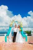 Hochzeitszeremonie auf einem tropischen Strand im Blau Glücklicher Bräutigam und Br Lizenzfreie Stockfotos