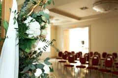 Hochzeitszeremoniehalle verzierte mit frischen Blumen Unscharfe St?hle f?r G?ste auf Hintergrund stockbild
