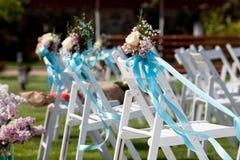 Hochzeitszeremoniestühle und ein Blumenstrauß von Rosen Stockbild