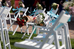 Hochzeitszeremoniestühle und ein Blumenstrauß von Rosen Stockfoto