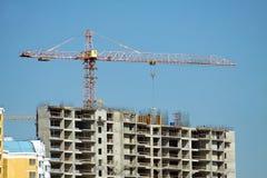 Hochziehen des Turmkrans und der Spitze des Baugebäudes Lizenzfreie Stockbilder