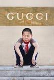 Hockender Junge vor einem Gucci-Shop, Xian, China Stockfotos