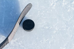 Hockey. Puck and stick on ice rink with copyspace