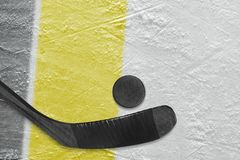 Hockey stick, puck and fragment of the ice arena with black and yellow lines. Hockey accessories on the ice hockey arena. Concept, hockey stock photography