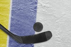 Hockey stick, puck and fragment of the ice arena with yellow and blue lines. Hockey accessories on the ice hockey arena. Concept, hockey, wallpaper royalty free stock photography