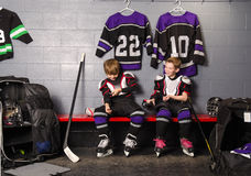 Hockey Arena Boys in Rink Dressing Room. Two Boys Get Dressed in hockey gear in dressing room before game Royalty Free Stock Photography