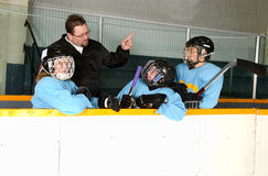 Hockey Coach on Bench With Players. A hockey coach teaches his players from the bench in the arena Royalty Free Stock Photo