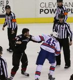 Hockey Fight. Referees watch as two hockey players exchange hits in the center rink fight royalty free stock images