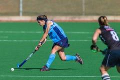 Hockey Girl Focus Hitting Ball  Stock Images