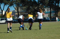Hockey girls. Four active caucasian female players running and playing a hockey game on the field outdoors stock images