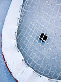 Hockey goal. Puck sitting on ice in back of hockey net after goal is scored Royalty Free Stock Photography
