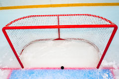 Hockey goal with puck on red line. View from above stock photography