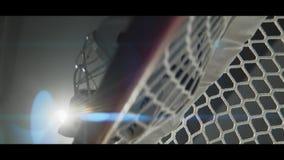 Hockey goalie mask on gate on dark stadium low angle shot. Hockey goalie protective mask lies on textile net of gate on ice arena in dark stadium low angle shot stock footage