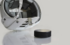 Hockey helmet and a hockey puck. Stock Images