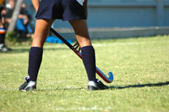 Hockey legs. The strong white legs of a sportive caucasian young woman playing Hockey sport in a team outdoors on a field Stock Photos