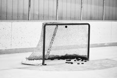 Hockey net full of pucks. Close up of a hockey net full of hockey pucks and blue goalie crease in front of yellow trimmed boards Stock Photos
