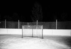Hockey net. On outdoor ice skating rink at night in black and white Stock Images