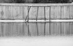 Hockey net in puddle of water. Hockey net in water from melting snow on outdoor ice skating rink Royalty Free Stock Image