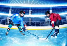 Hockey opponents challenging for puck at stadium. Portrait of two teenage boys, professional hockey players, challenging for the puck at stadium stock image