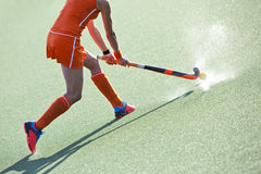 Hockey pass. Female field hockey player passing to a team mate on a modern, water artificial astroturf field Royalty Free Stock Photo