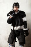 Hockey Player. In front of concrete block wall stock photography