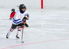 Hockey Player in Action. A young hockey player races with the puck, leaving the other team on their knees stock photography