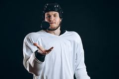 Hockey player bites the puck with broken teeth and looking at camera with a grin. stock image
