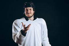 Hockey player bites the puck with broken teeth and looking at camera with a grin. Hockey players shoots the puck and attacks stock images