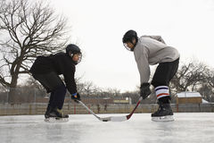 Hockey player face off. Two ice hockey player boys in uniform facing off on ice stock photography