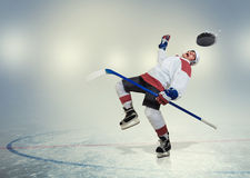 Hockey player falls down on ice Stock Photos