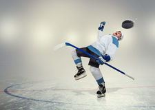 Hockey player falls down on ice Stock Photo