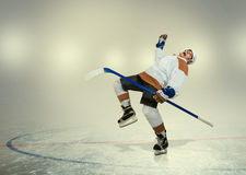 Hockey player falls down on ice Stock Image