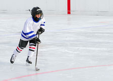 Hockey Player on Ice. A young hockey player races with the puck royalty free stock images