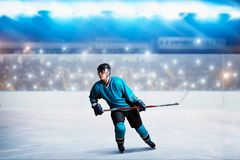 One hockey player on ice in action, arena. A hockey player on ice in action, arena spotlights and tribunes with fans on background. Male person in helmet, gloves stock photos