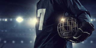 Hockey player on ice . Mixed media. Hockey player in blue uniform on ice rink in spotlight royalty free stock photography