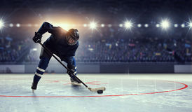 Hockey player on ice . Mixed media. Hockey player in blue uniform on ice rink in spotlight royalty free stock images