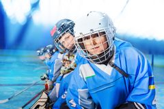 Hockey player practicing with teammate on ice rink. Portrait of young hockey player wearing protective equipment, practicing with teammates on ice rink royalty free stock photography