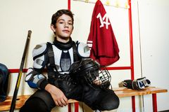 Hockey player preparing for game in locker room. Close-up portrait of teenage boy in protective equipment sitting on the bench in men`s ice hockey locker room royalty free stock images