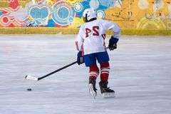 Hockey player with a puck on the ice of the blade moves the ice. stock photography