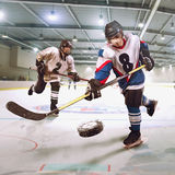 Hockey player shoots the puck and attacks the goalkeeper stock image