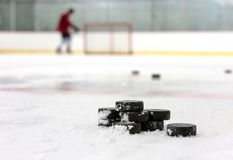 Hockey player with stack of pucks. A hockey player skates in the background as pucks are stacked in the foreground Royalty Free Stock Photos