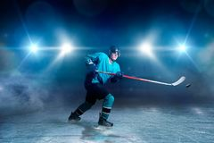 Hockey player with stick and puck makes a throw. Ice arena, spotlights on background royalty free stock photo