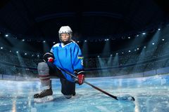 Hockey player with stick standing on one knee. Portrait of young hockey player with stick standing on one knee on ice rink royalty free stock images