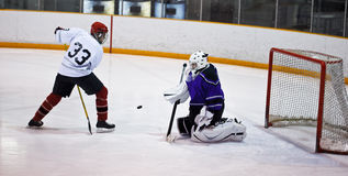 Hockey player trick shot. Hockey player taking a shot on net with a trick shot manoeuver stock photography