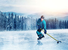Hockey player in uniform on frozen lake. Winter forest on background. Ice-skating outdoors Stock Images