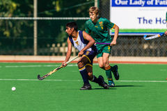 Hockey Players DHS Ball Challenge. Hockey Durban Boys High Player with the ball while being challenged. First teams high school derby game between rivals Stock Photo